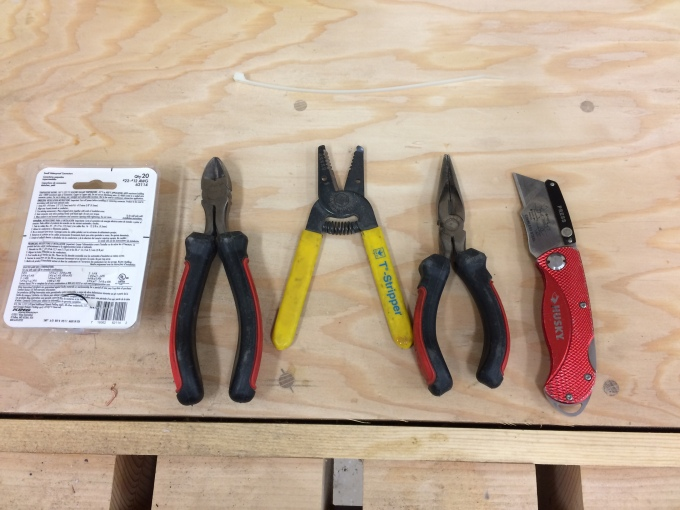 "Tools for the wiring hookup. From left to right, you have the waterproof wire nuts, a set of ""dikes"", wire stripper, needle nose pliers, and a utility knife."