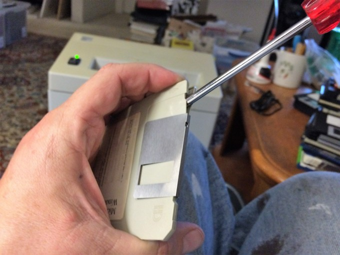 Pry the disk cover open by inserting a screwdriver near the metal slide.