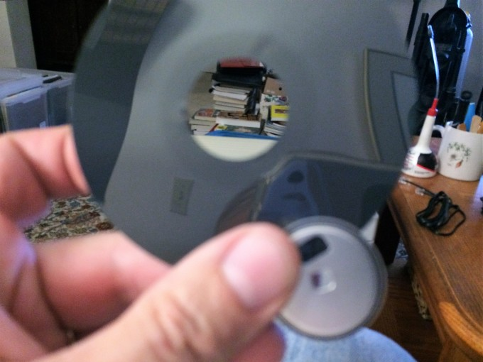 Tear the metal center out from the magnetic film of the disk.
