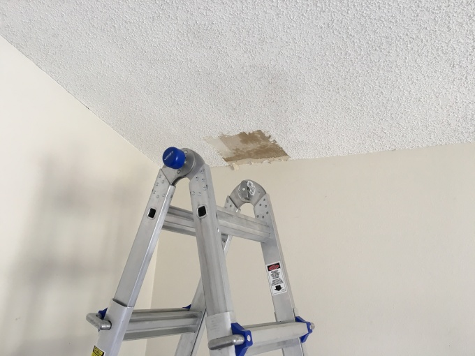 First section of asbestos popcorn removed. Note that the ceiling is saturated with water in the area that I'm working.