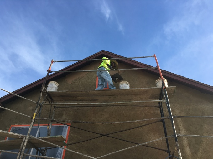 Color coat being applied over existing stucco (right under the eaves).